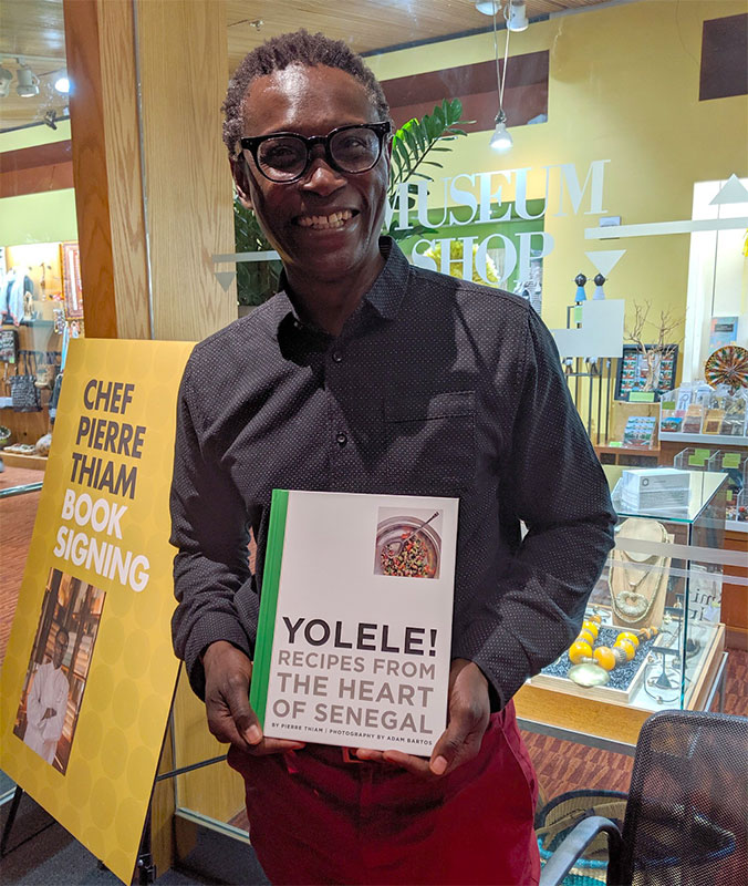 Chef Pierre Thiam holding his book of recipes fron Senegal