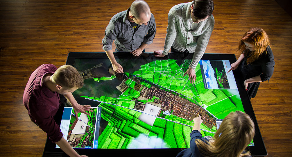 3 males and 2 females simultaneously interact with an Ideum Colossus Multitouch Table.