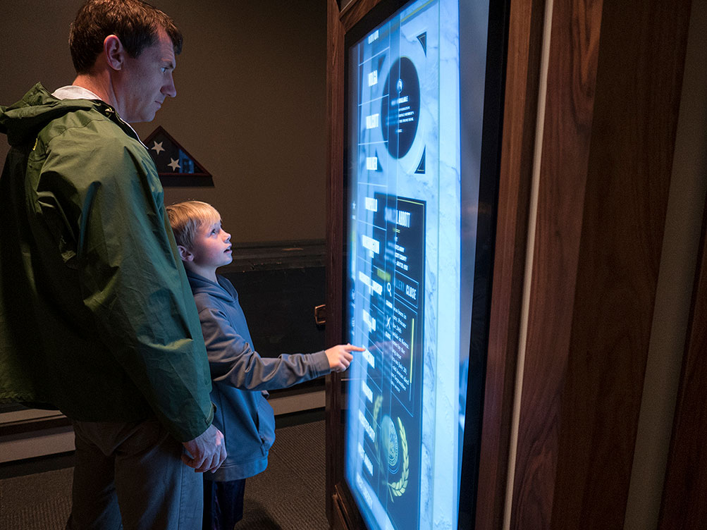 Boy and Adult explore Faces of the Fallen on an Ideum 65-inch Presenter display.