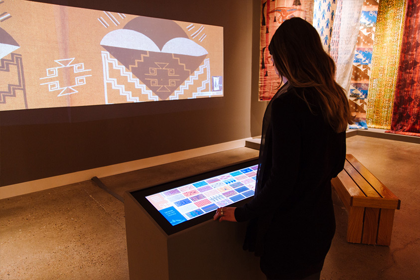 A woman stands before a custom Ideum 38-inch stretch touch monitor which serves as a control console for the Lloyd Kiva New textile exhibition.