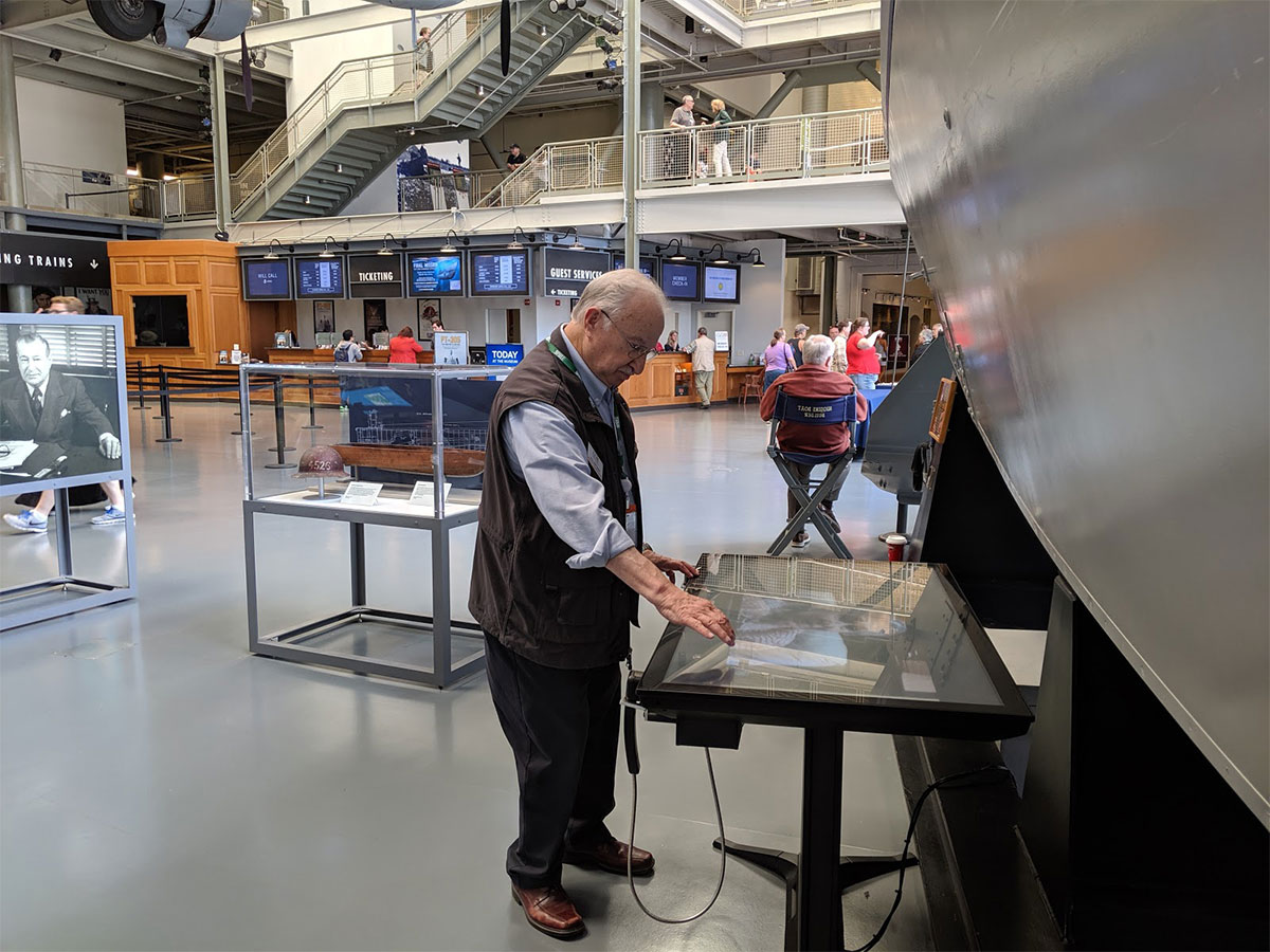 Man interacts with an Ideum multitouch table equipped with custom sound wands.