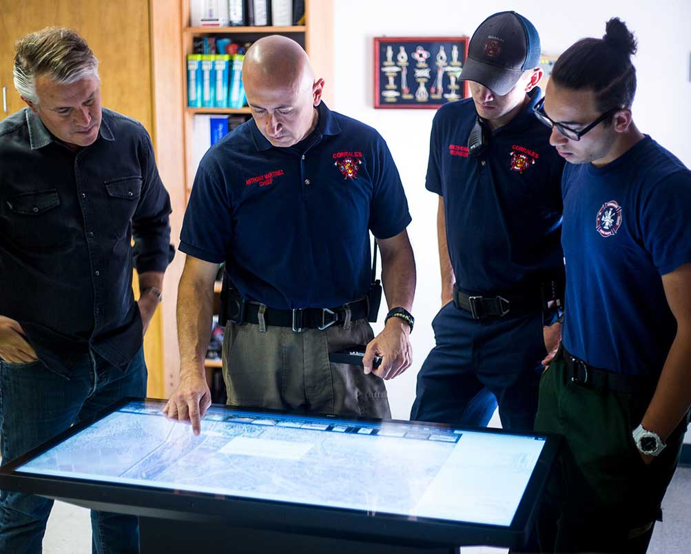 Ideum touch table being used by members of the Corrales Fire Department
