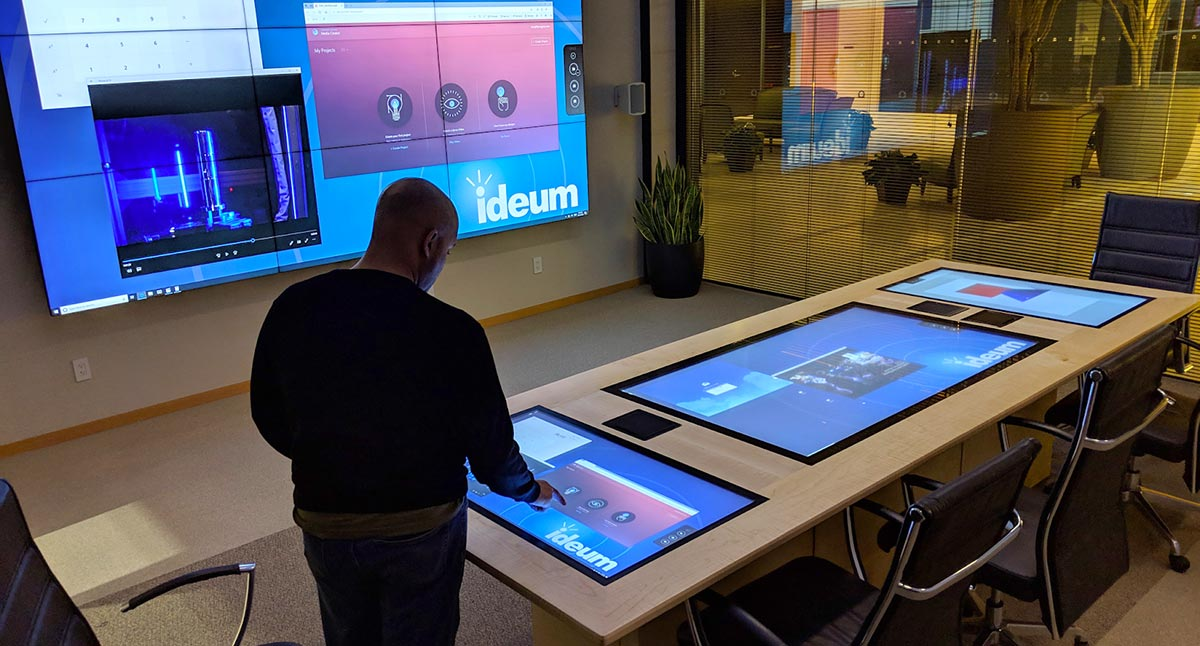 Man interacts with a wooden conference table that has inline touch displays.