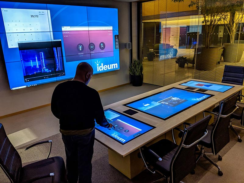 Man standing before a custom Ideum multitouch conference room table.