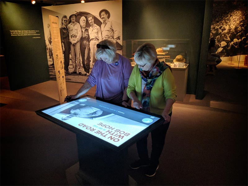 Two women interecting with an Ideum touch table in the On the Road with Bob Hope exhibit.