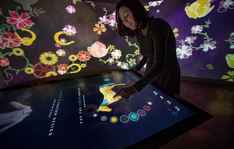 Young woman interacts with touch table running Cowgirl app.