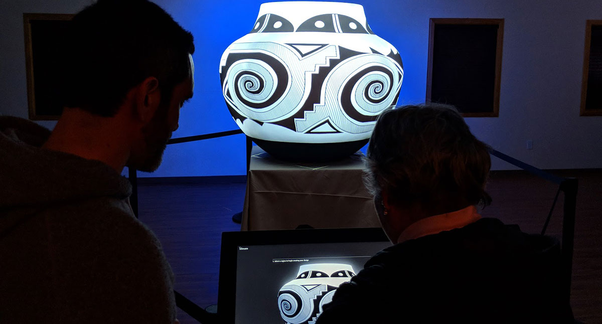 A man and woman use a touch display to control the projection of Acoma Pueblo pottery designs onto a complex curved surface.