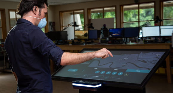 A person uses touchless gestures on an Ideum Drafting table to control and interactive application.