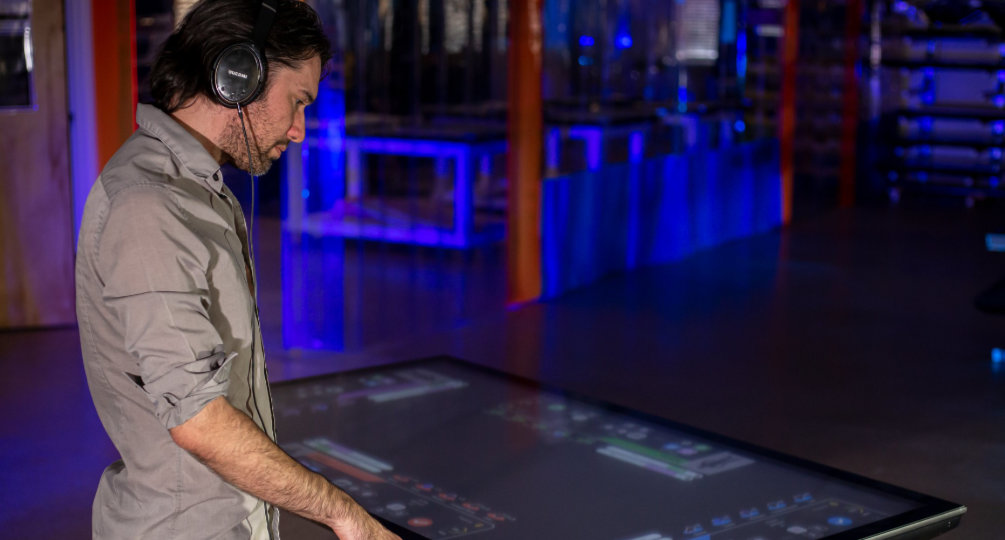 Man wearing headphones ineracts with touch Table.