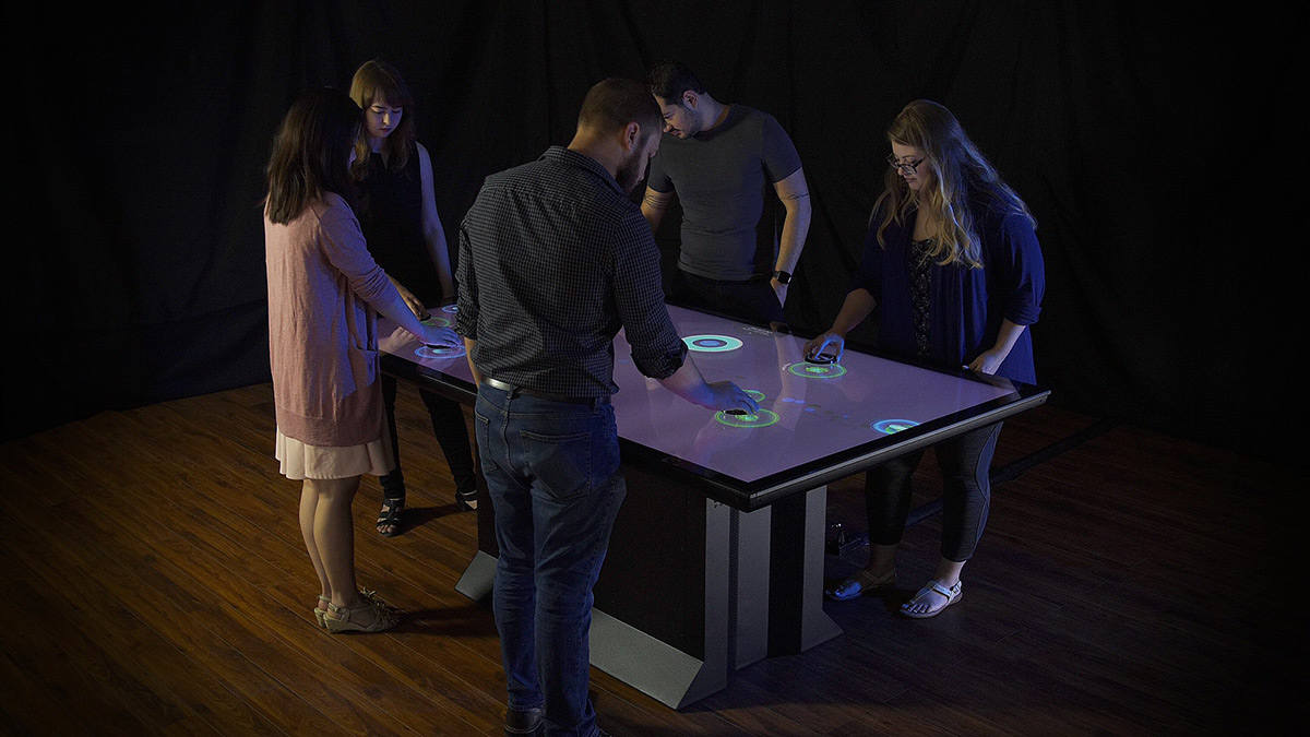Five people interacting with a multitouch table.
