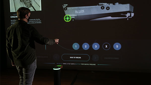 A visitor uses gestures to interact with a touchless pedestal which manipulates a large display.