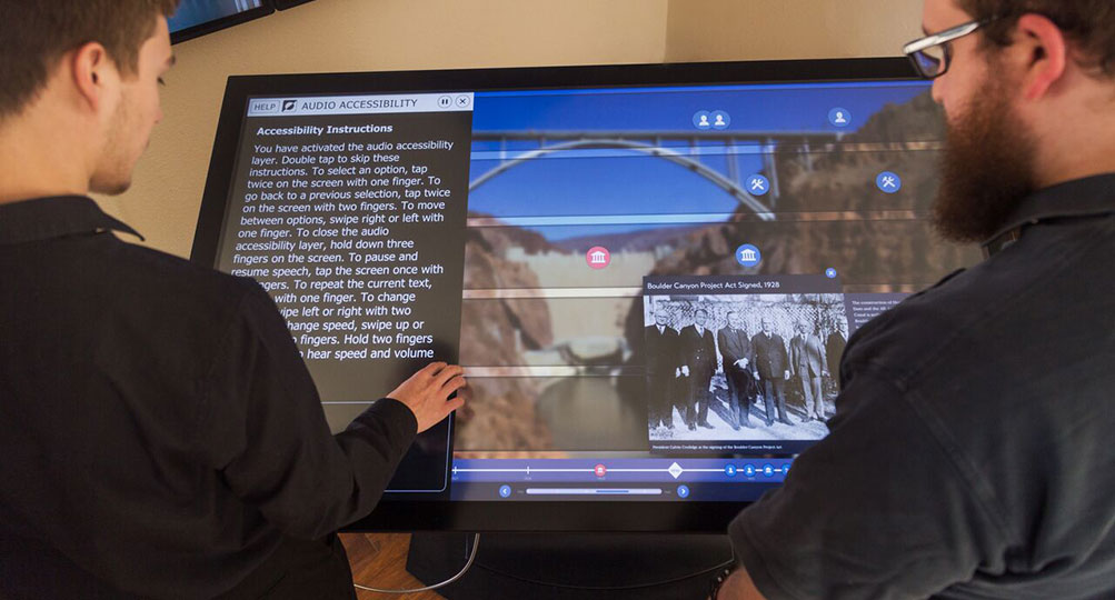 hereTwo men stand at a touch table. The man on the left touches the screen to control the accessibility layer. The man on the right observes video.