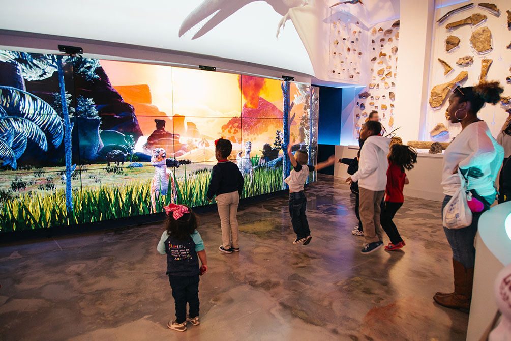 Visitors interact with Dinosaurs on a massive video wall.