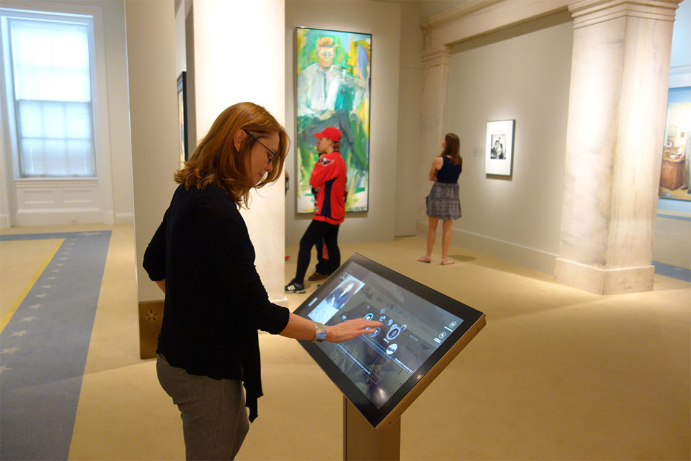 Woman interacts with a custom touch display at the National Portrait gallery.
