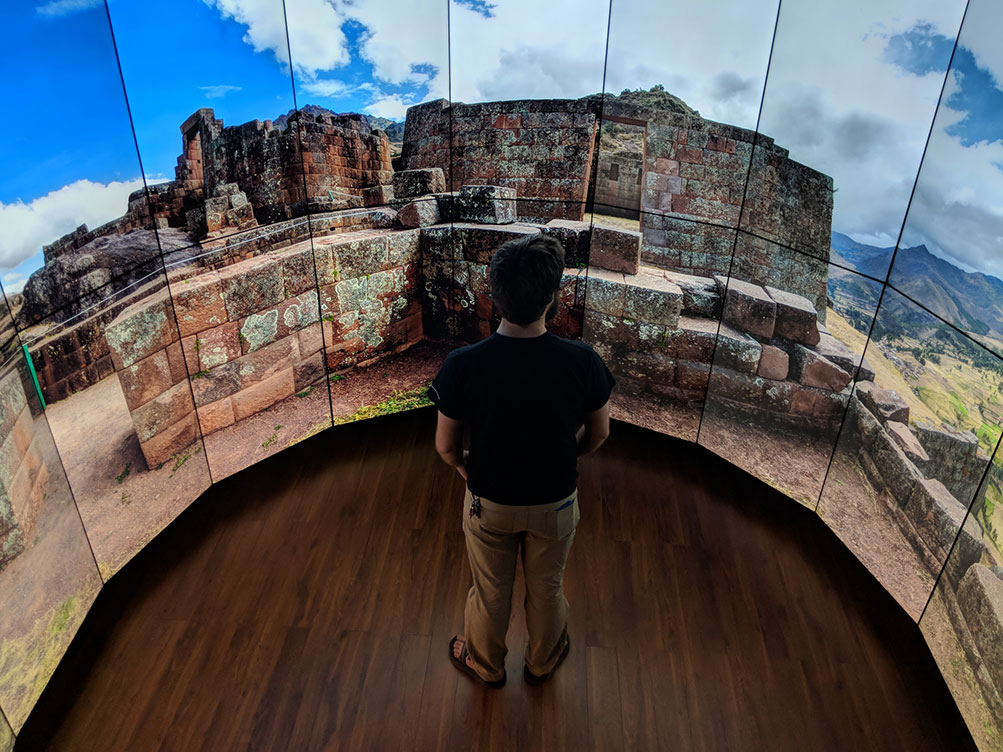 A man stands before an image of ruins from Cusco.